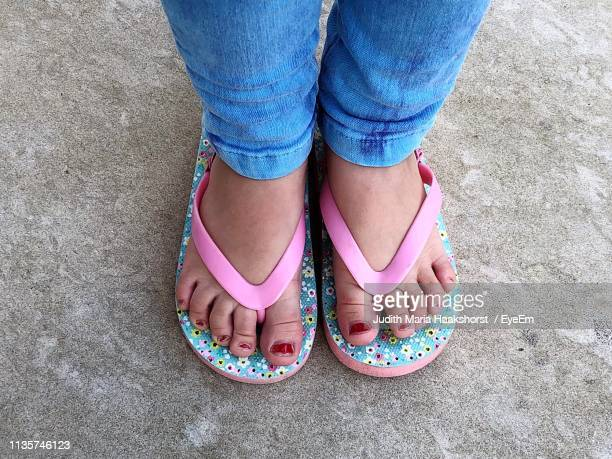 low section of girl wearing flip-flops on footpath - open toe stock pictures, royalty-free photos & images