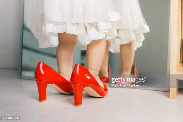 Low Section Of Girl Wearing Red Shoes