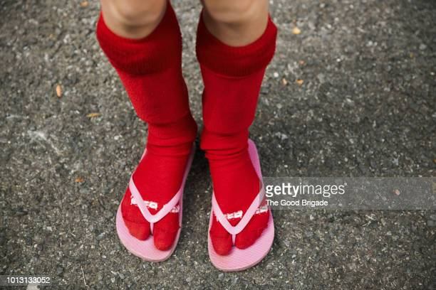 low section of girl wearing red socks and flip flops - fashion oddities stock pictures, royalty-free photos & images