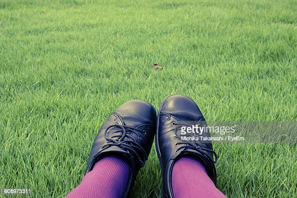 low section of girl wearing shoes at grassy field - black shoe stock photos and pictures