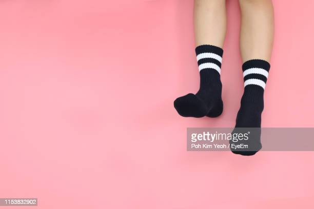 low section of girl wearing socks while resting over colored background - sock stock pictures, royalty-free photos & images