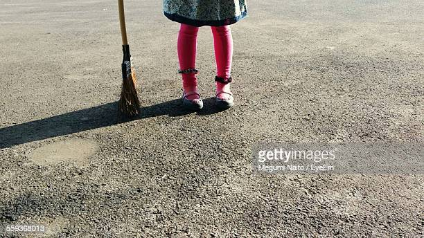 Low Section Of Girl With Broom On Concrete Flooring On Sunny Day