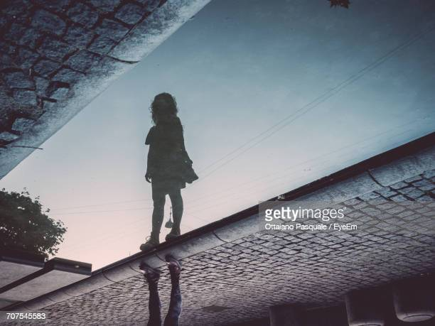 Low Section Of Girl With Reflection On Puddle At Street