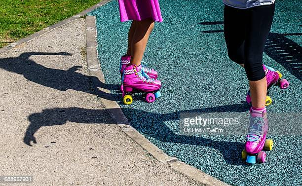 Low Section Of Girls Balancing On Roller Skate At Park