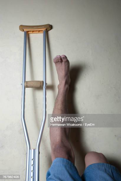 Low Section Of Handicapped Man With Crutch On Floor