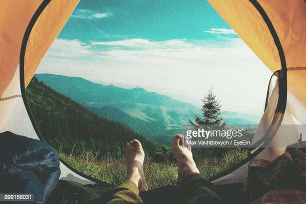 Low Section Of Hiker Lying In Tent Against Mountains