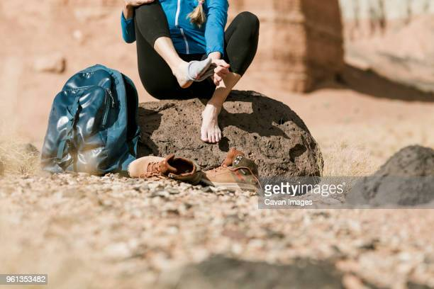Low section of hiker removing sock while sitting on rock at desert