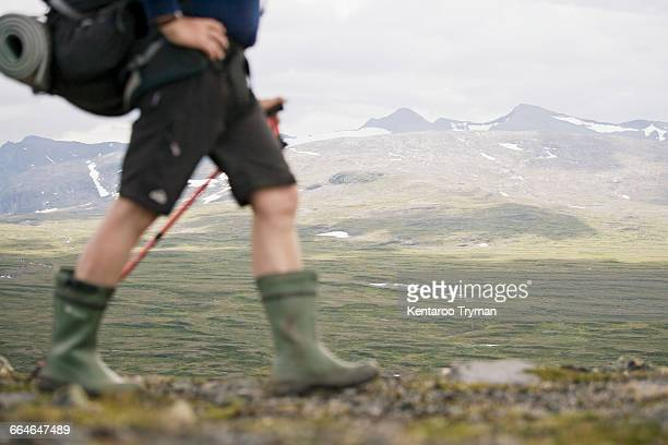 Low section of hiker walking against mountains