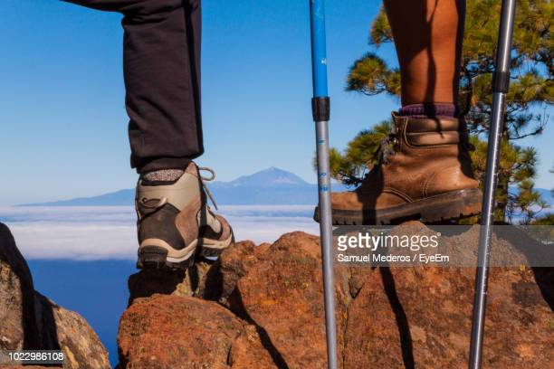 Low Section Of Hikers Standing With Hiking Poles On Rocks Against Clear Blue Sky
