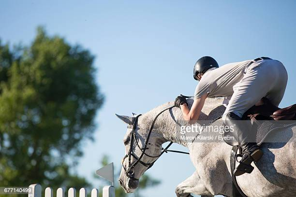 Low Section Of Jockey Jumping Horse Against Sky