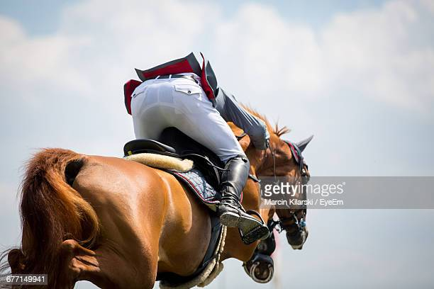 low section of jockey jumping horse against sky - equestrian event stock pictures, royalty-free photos & images