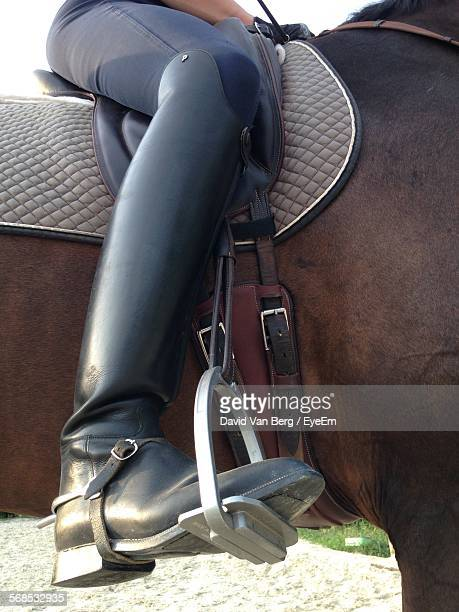 Low Section Of Jockey Sitting On Horse With Spur