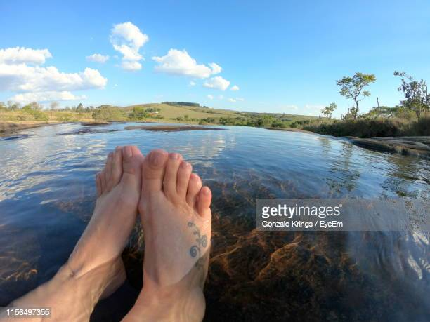 low section of leg relaxing on lake - krings stock pictures, royalty-free photos & images