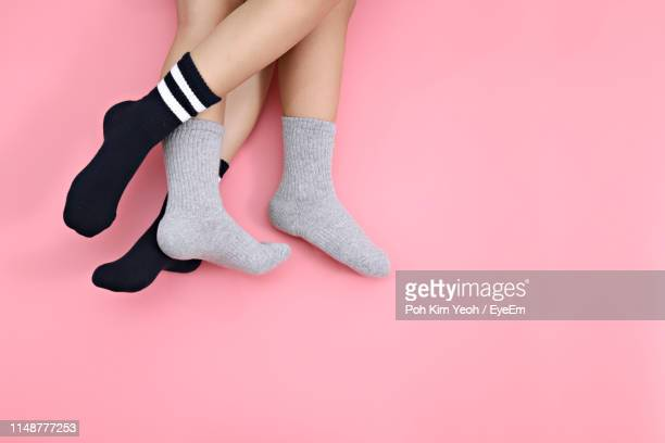 low section of lesbian couple wearing socks over pink background - pair stock pictures, royalty-free photos & images