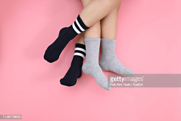 low section of lesbian couple wearing socks over pink background - sock stock pictures, royalty-free photos & images