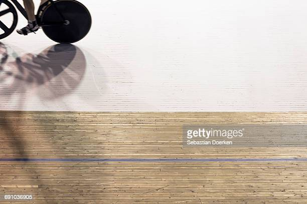 low section of male athlete riding bicycle in velodrome - track cycling stock pictures, royalty-free photos & images