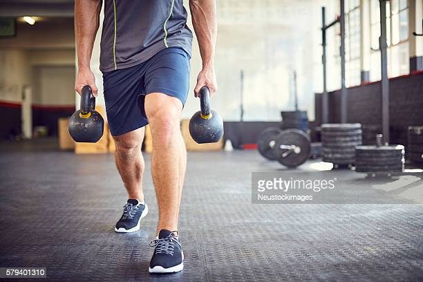 Low section of male lifting kettlebell on gym floor
