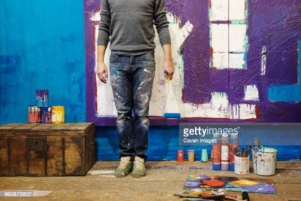 Low section of male painter holding paint roller and standing against wall