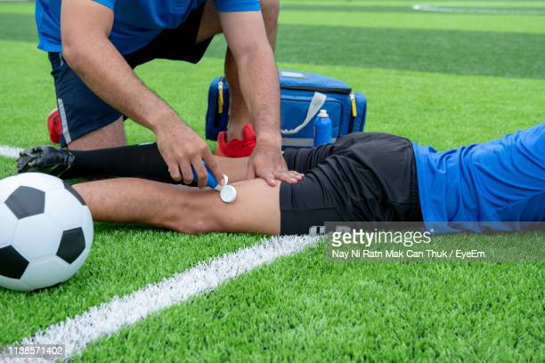 low section of male physical therapist applying ointment on soccer player leg at field - sports medicine stock pictures, royalty-free photos & images