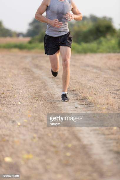 Low section of male runner jogging on dirt path