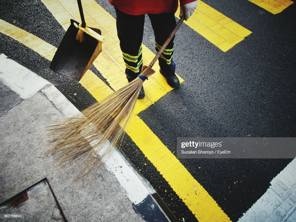 Low Section Of Male Sanitation Worker Sweeping Road : Stock Photo