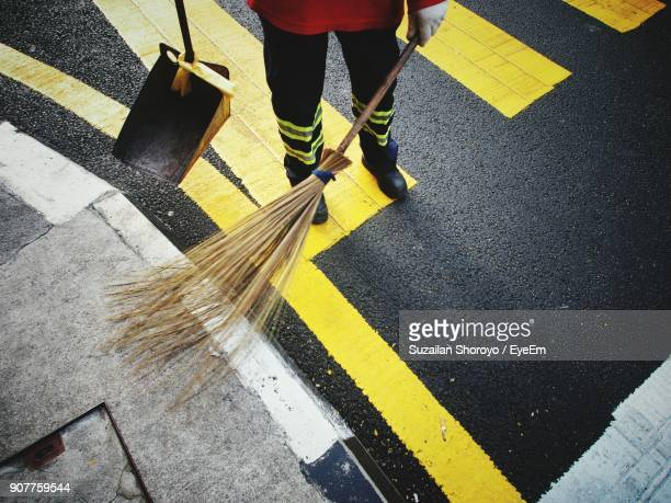 Low Section Of Male Sanitation Worker Sweeping Road