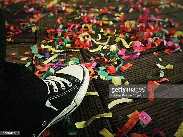 Low Section Of Man Against Colorful Papers On Ground