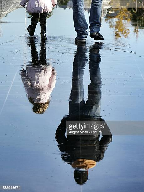 Low Section Of Man And Daughter Walking With Reflection In Puddle