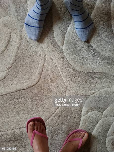 Low Section Of Man And Woman On Rug At Home