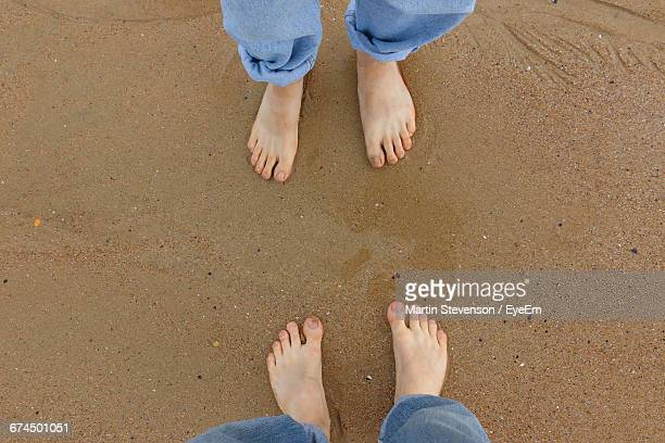 Low Section Of Man And Woman Standing At Sea Shore