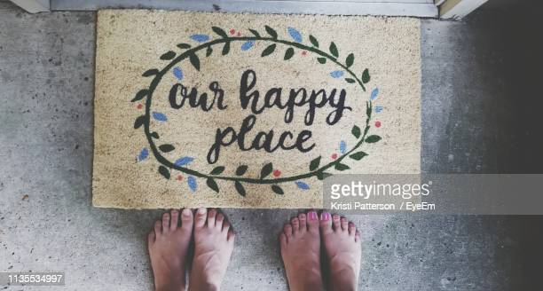 low section of man and woman standing in front of doormat with text - human doormat foto e immagini stock