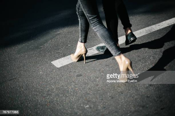 low section of man and woman walking on road - high heels stock pictures, royalty-free photos & images