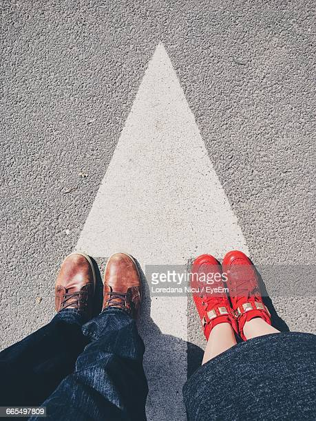 Low Section Of Man And Woman Wearing Shoes Standing On Road With Arrow Sign