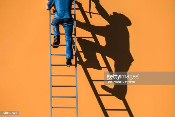 low section of man at sunset - ladder stock pictures, royalty-free photos & images