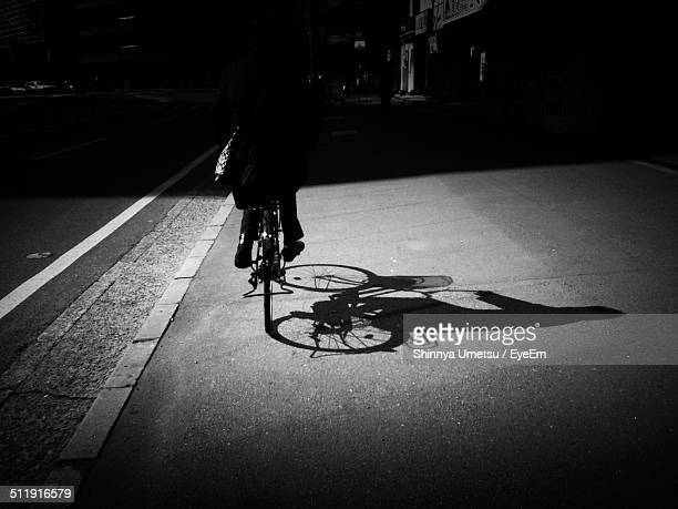 Low section of man bicycling on road