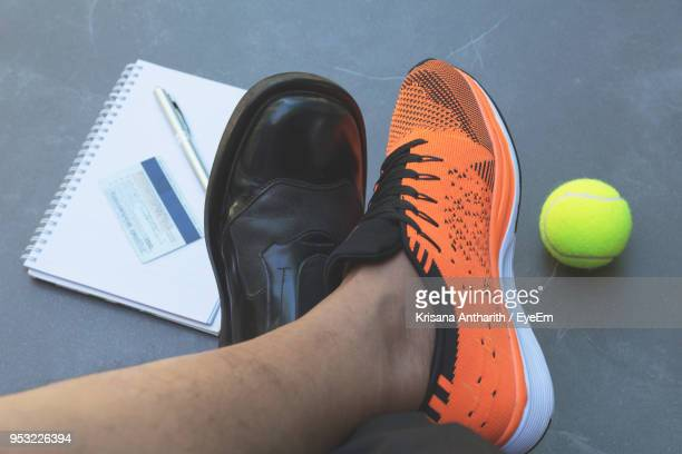 low section of man by tennis ball and book - charging sports stock photos and pictures