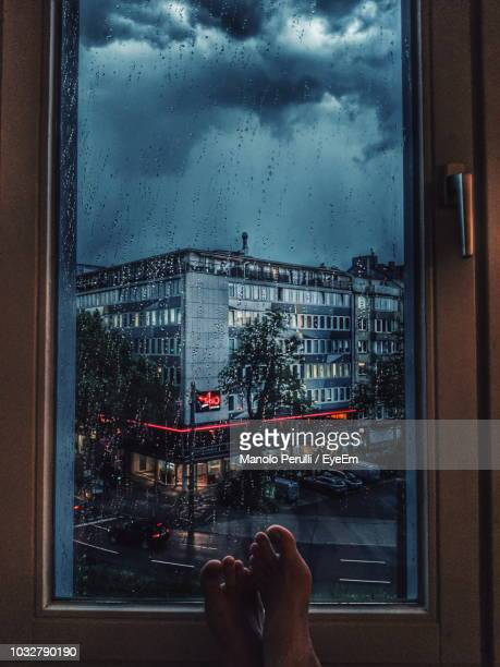 low section of man by wet window in city during rain - regentropfen stock-fotos und bilder