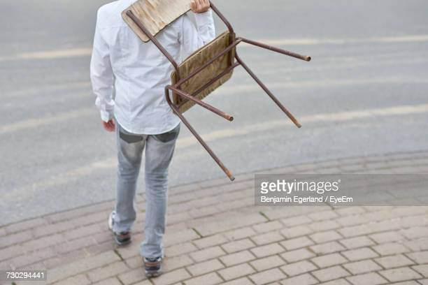 low section of man carrying chair on street - carrying fotografías e imágenes de stock