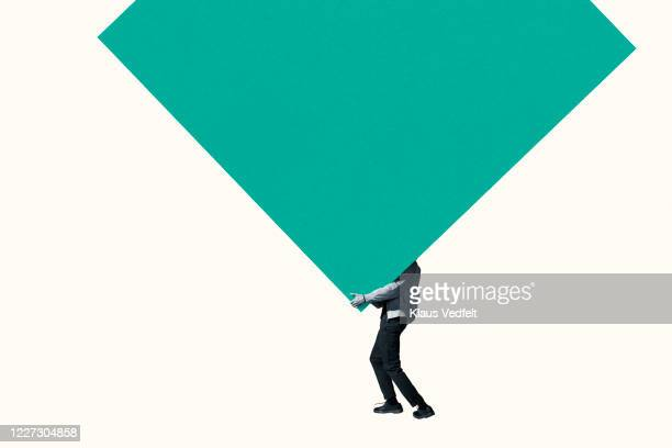 low section of man carrying large green block - バイアス ストックフォトと画像