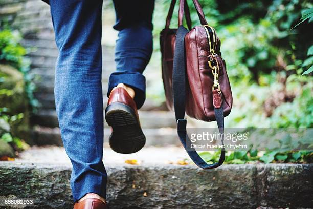 low section of man carrying leather bag - strap stock photos and pictures