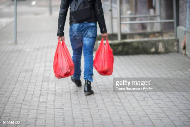 low section of man carrying plastic bags while walking on sidewalk - ビニール袋 ストックフォトと画像