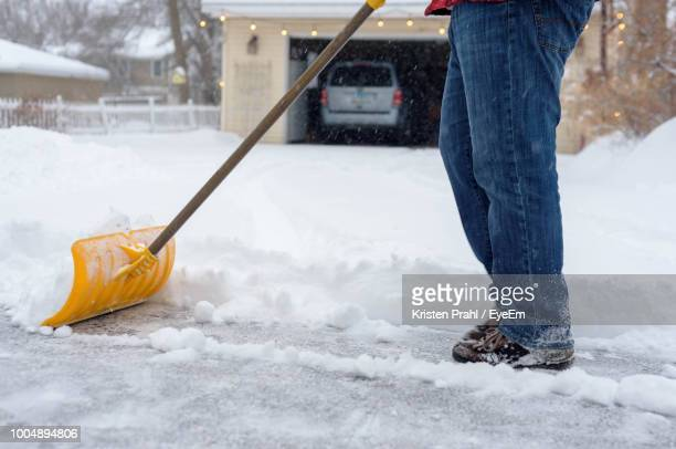 Low Section Of Man Cleaning Snow On Road
