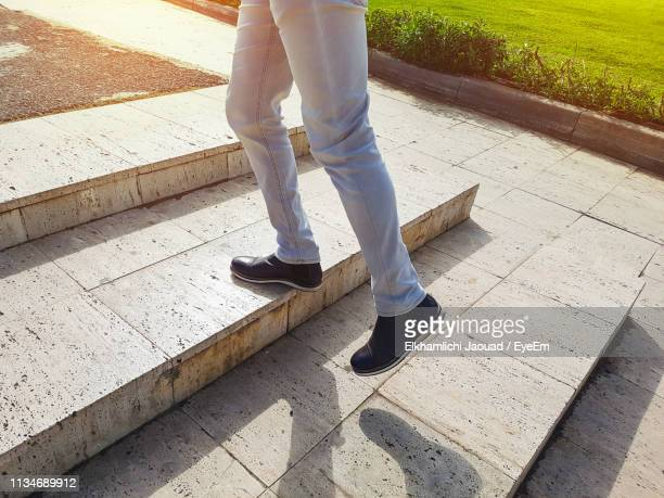 low section of man climbing steps in park - 人の足 ストックフォトと画像
