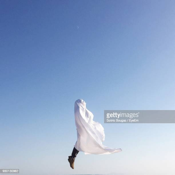 Low Section Of Man Covered With Cloth Jumping Against Clear Blue Sky