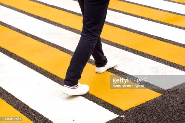 low section of man crossing road - lower stock pictures, royalty-free photos & images