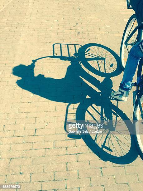 Low Section Of Man Cycling With Shadow On Footpath