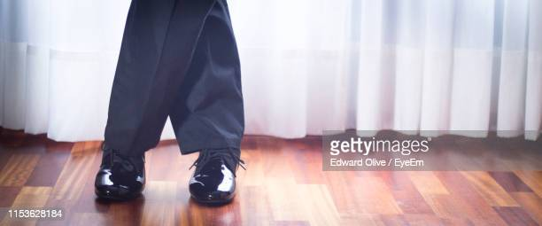low section of man dancing in hall - mens dress shoes stock pictures, royalty-free photos & images