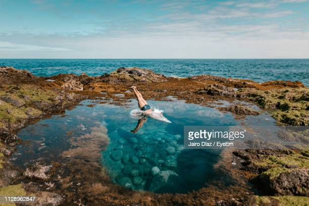 low section of man diving in sea surrounded by rocks against sky - islas canarias fotografías e imágenes de stock