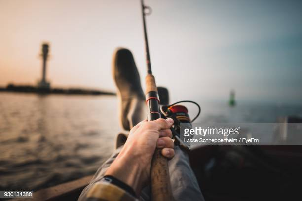 Low Section Of Man Fishing In Sea Against Sky During Sunset