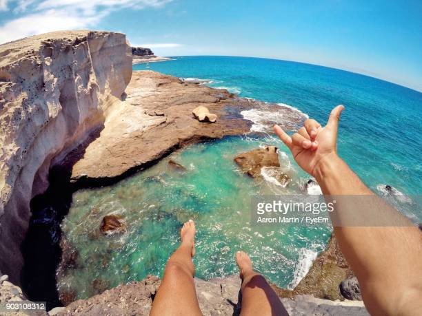 low section of man gesturing shaka sign on cliff against sea - wide angle stock pictures, royalty-free photos & images
